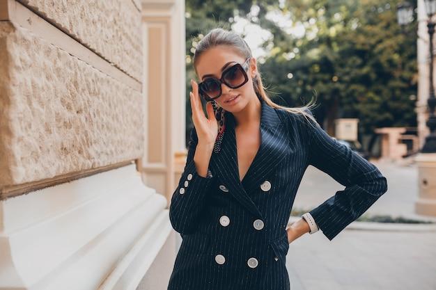 Elegante donna sexy vestita in abito da smoking elegante che cammina in città il giorno di primavera estiva
