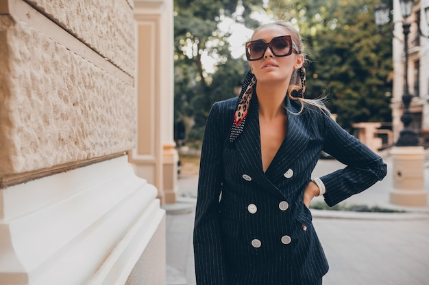 Stylish sexy woman dressed in elegant tuxedo suit walking in city on summer spring day