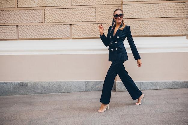 Стильная сексуальная женщина, одетая в элегантный смокинг, гуляет по городу в летний весенний день