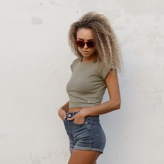 Стильная сексуальная молодая красивая кудрявая девушка в солнцезащитных очках в модной футболке и джинсовых шортах стоит у белой стены