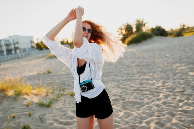 Стильная стройная девушка с ретро камерой позирует на солнечном вечернем пляже. летний отпуск. тропическое настроение. концепция свободы и путешествий.