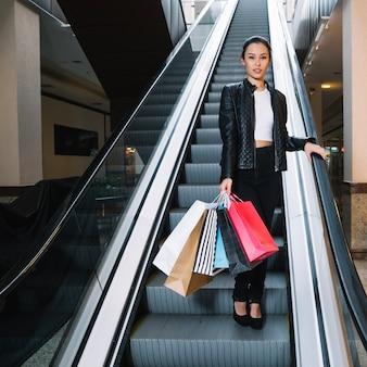 Elegante acquirente in posa sulla scala mobile