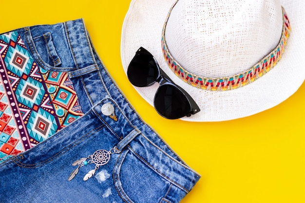Stylish short denim shorts with a boho pattern and a dream catcher black sunglasses and white straw hat isolated on a bright color yellow wall