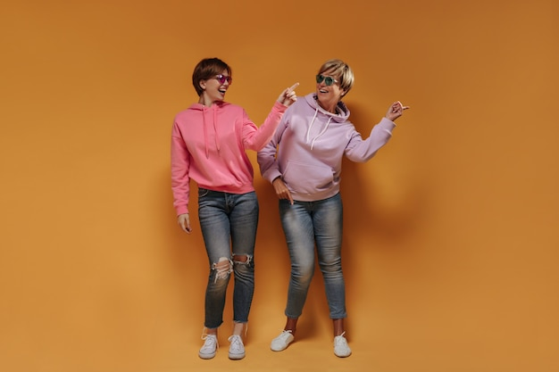Stylish short haired ladies in bright glasses, wide hoodies, white sneakers and skinny jeans dancing and smiling on orange backdrop.