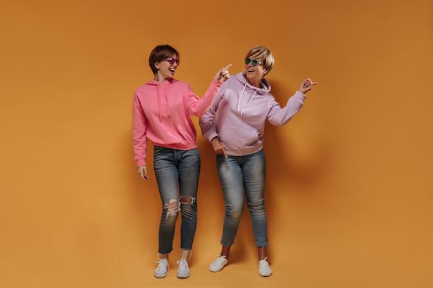 明るいメガネ、ワイドパーカー、白いスニーカー、スキニージーンズを身に着けたスタイリッシュなショートヘアの女性が、オレンジ色の背景で踊り、笑顔を見せています。