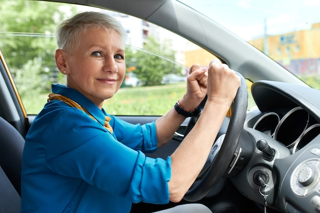 Stylish short haired middle aged businesswoman sitting in driver's seat clenching fists, being stuck in traffic jam