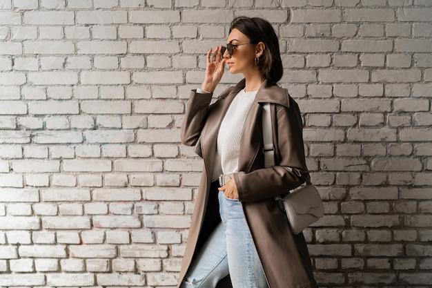 Elegante donna dai capelli corti in cappotto di pelle casual e jeans in posa su un muro di mattoni urbano