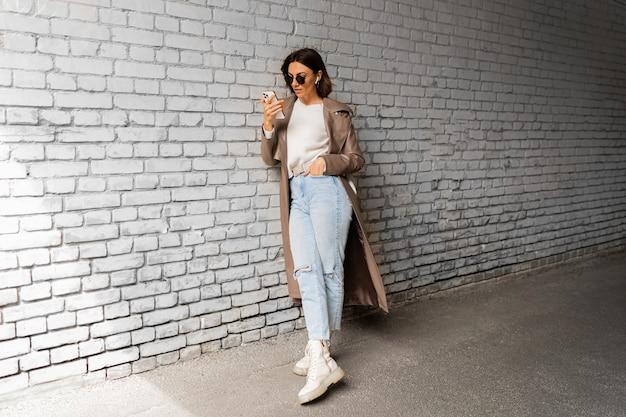 Elegante donna dai capelli corti con auricolari in cappotto di pelle casual e occhiali da sole che utilizza smartphone e posa su un muro di mattoni urbano