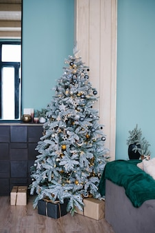 Stylish silver christmas tree with golden toys in the living room interior in blue mint tones