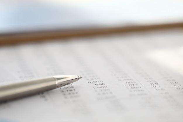 세련된 실버 펜은 숫자가있는 보고서에 달려 있습니다.