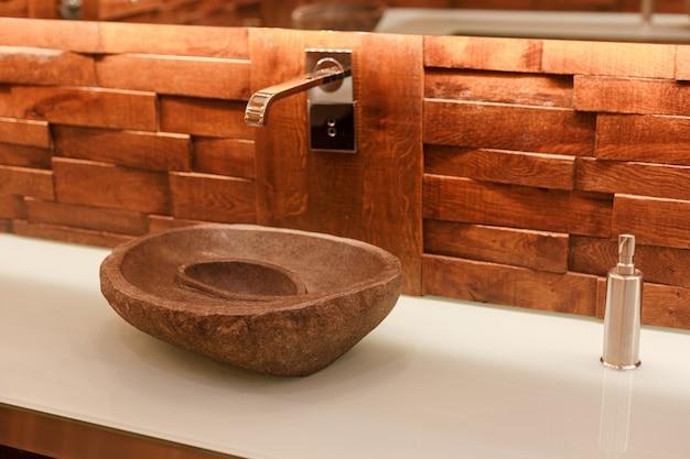 가벼운 천연석으로 만든 세련된 싱크대. 열대 로프트 스타일의 나무 위에 석재 세면대가있는 욕실.