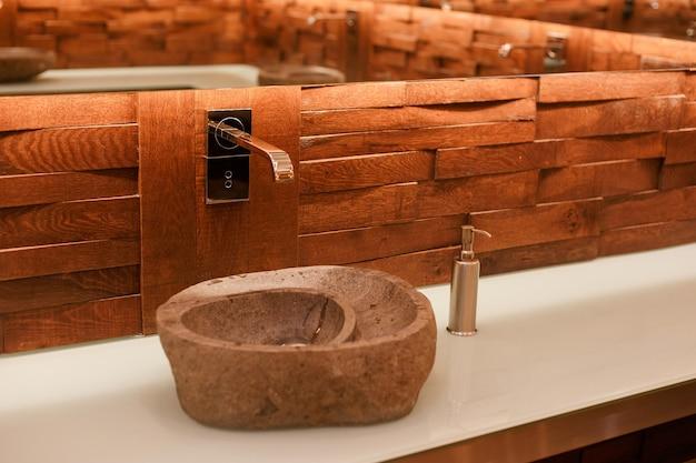 軽い天然石で作られたスタイリッシュなシンク。トロピカルロフトスタイルの木製トップに石の洗面台を備えたバスルーム。