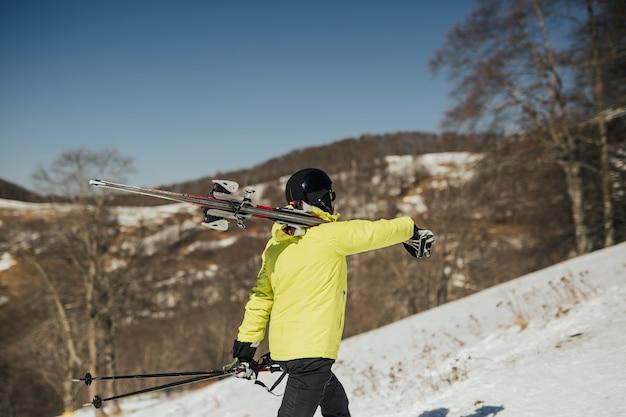 黒のスキーマスクと緑のジャケットを着たスタイリッシュなスキーヤーが、スキーを肩に乗せて行きます