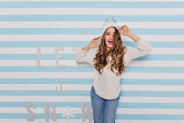 Стильная, стройная модель с темными волосами смеется и счастливо позирует. портрет девушки в белой одежде на стене с красивым текстом