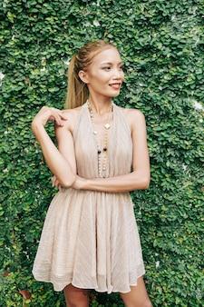 멀리보고 웃 고 fower 정원의 녹색 울타리에 서있는 세련 된 슬림 젊은 여성