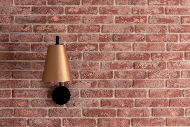 Stylish small golden lamp sconce installed on red brick wall against brown window curtain in contemporary apartment room closeup. interior design details.