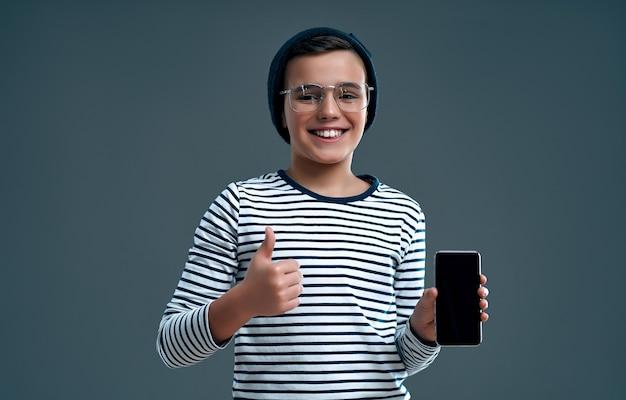 Стильный умный ребенок-школьник в шляпе и очках со смартфоном показывает большой палец вверх, изолированный на сером.