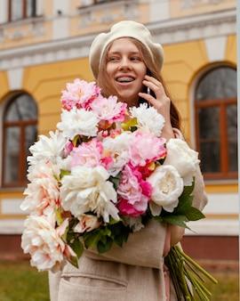 Elegante donna sorridente che tiene il mazzo di fiori all'aperto in primavera e parlando al telefono