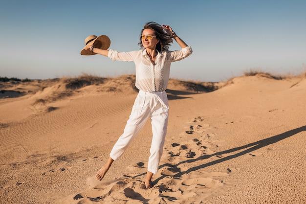 夕焼けに麦わら帽子をかぶって白い服を着て砂漠の砂を走ってジャンプするスタイリッシュな笑顔の美しい幸せな女性