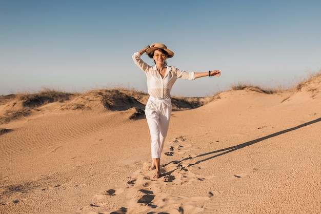 Stylish smiling beautiful happy woman running and jumping in desert sand in white outfit wearing straw hat on sunset