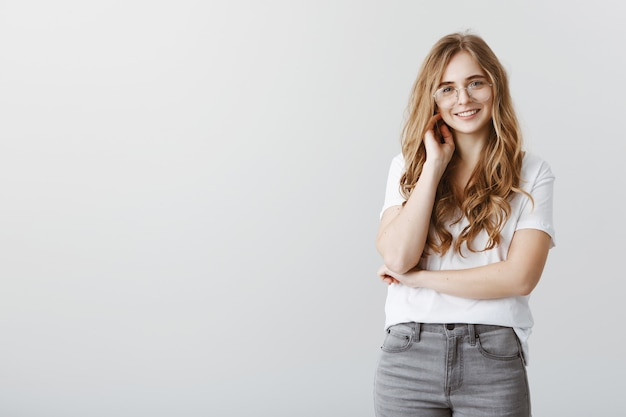Stylish smiling blond female student over grey wall