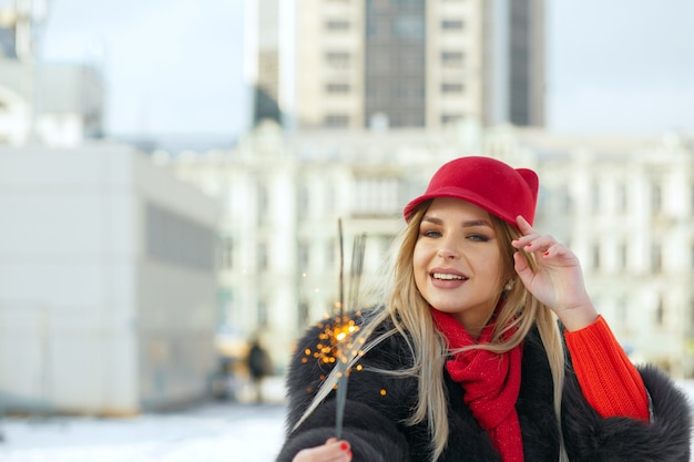 Stylish smiling blonde girl wearing fashionable red cap and scarf celebrating christmas with sparklers at the street. space for text