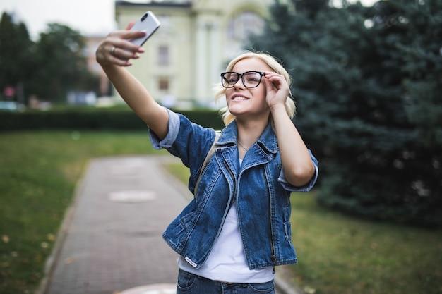 ジーンズスイートでスタイリッシュな笑顔のファッションブロンドの女の子女性は、朝市の彼女の電話でselfieを作る