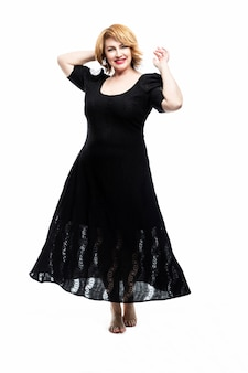 Stylish smiling middle-aged woman in a black flying dress on a white wall. healthy lifestyle and activity. vertical.