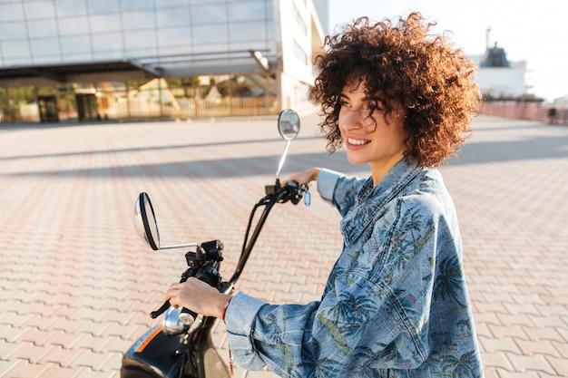 屋外のモダンなバイクに座っているスタイリッシュな笑顔の女性