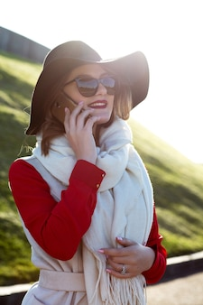 公園で携帯電話で話している帽子と眼鏡をかけているスタイリッシュな笑顔の女性