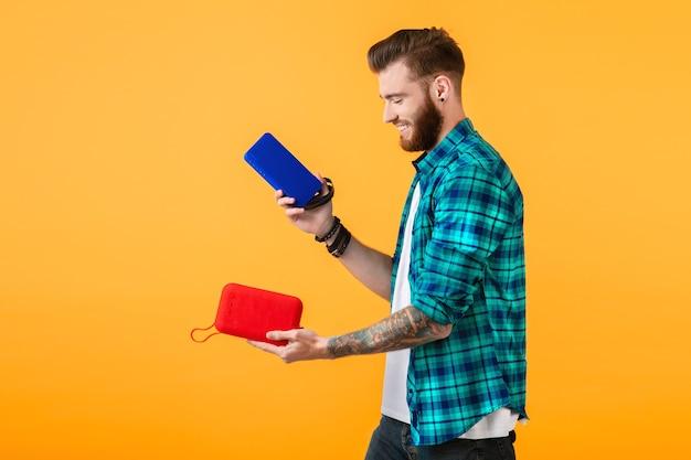 Стильный улыбающийся молодой человек, держащий беспроводной динамик, счастлив слушать музыку в красочном стиле, счастливое настроение, изолированное на желтой стене