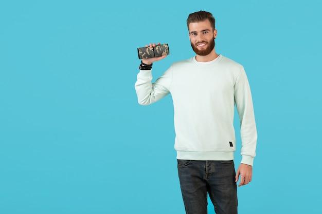 Стильный улыбающийся молодой человек, держащий беспроводной динамик, слушая музыку в красочном стиле, счастливое настроение, изолированное на синей стене