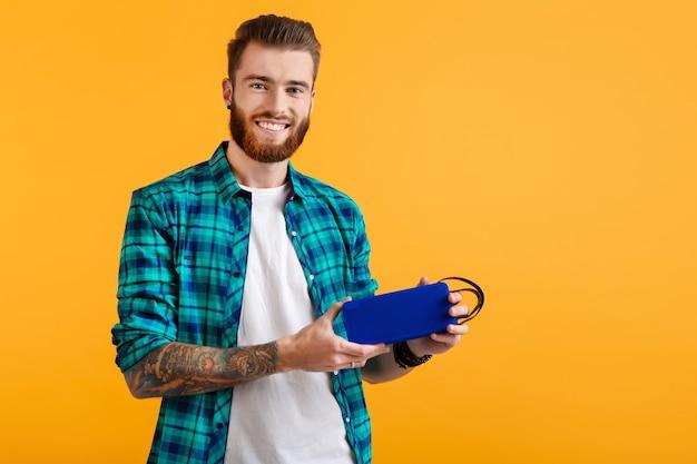 Стильный улыбающийся молодой человек, держащий беспроводной динамик, слушая музыку в красочном стиле, счастливое настроение, изолированное на желтом фоне