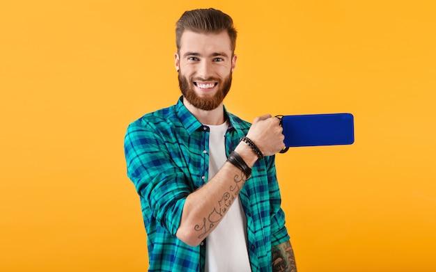 オレンジ色の音楽を聴いてワイヤレススピーカーを保持しているスタイリッシュな笑顔の若い男