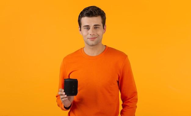 オレンジ色のセーターでスタイリッシュな笑顔の若い男は、オレンジ色で楽しんで音楽を聴いて幸せなワイヤレススピーカーを保持