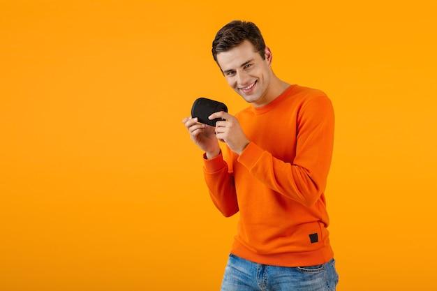 ワイヤレス スピーカーを保持しているオレンジ色のセーターを着たスタイリッシュな笑顔の若い男が楽しんで音楽を聴いて幸せ