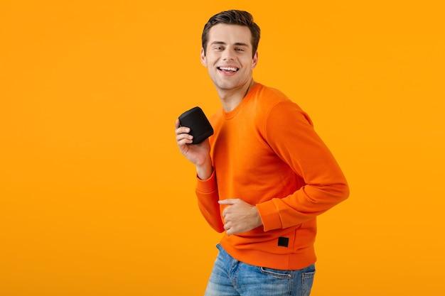 Стильный улыбающийся молодой человек в оранжевом свитере, держащий беспроводную колонку, счастлив, слушая музыку, весело проводя время