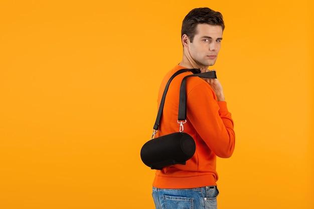 Стильный улыбающийся молодой человек в оранжевом свитере с беспроводным динамиком счастлив, слушая музыку
