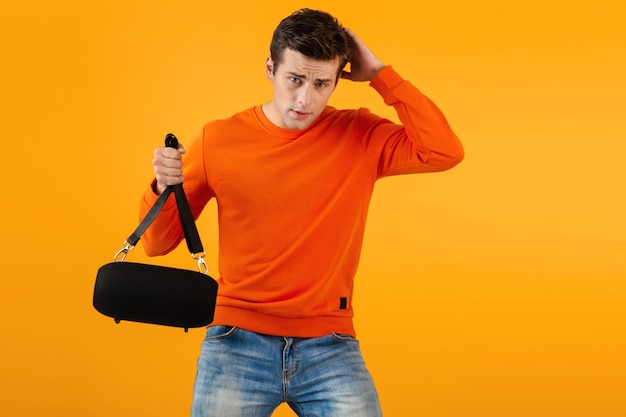 音楽を聞いて幸せなワイヤレススピーカーを保持しているオレンジ色のセーターでスタイリッシュな笑顔の若い男
