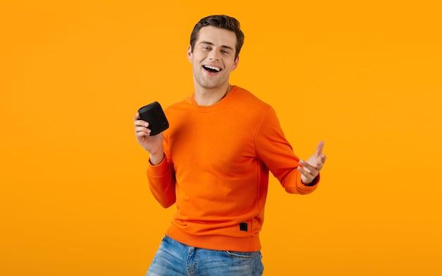 Giovane sorridente alla moda in maglione arancione che tiene altoparlante senza fili felice ascoltando musica divertendosi sull'arancio