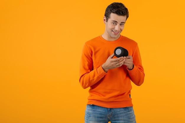 Elegante giovane sorridente con un maglione arancione che tiene in mano un altoparlante wireless felice ascolto di musica divertendosi