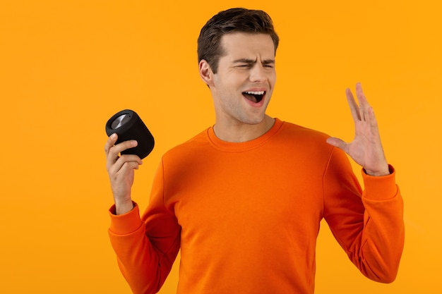 Stylish smiling young man in orange sweater holding wireless speaker happy listening to music
