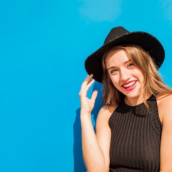 Stylish smiling young woman in front of wall