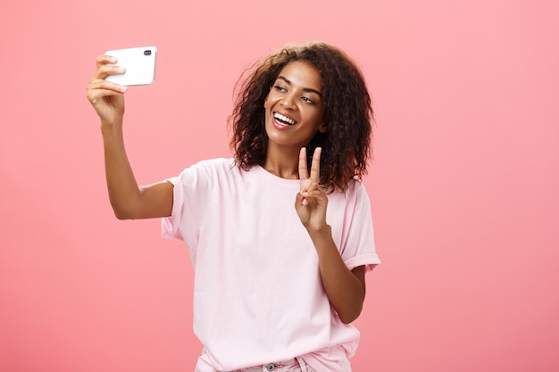 Stylish sociable goodlooking dark skinned female student with curly hairstyle pulling hand with smartphone near face taking selfie showing peace sign to device screen while smiling carefree