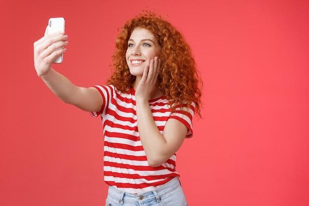 Стильная женщина в социальных сетях популярный блоггер обожает фотографировать себя протягивает руку, удерживая смартфон, позирует глупо милой летней одежде, делает селфи улыбающимся нежным экраном телефона на красном фоне.