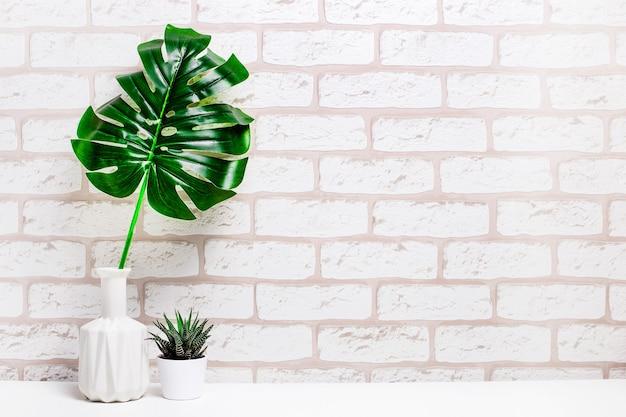 花瓶にモンステラの葉、自宅の小さな鉢植え、または棚に白いレンガの背景があるスタジオのスタイリッシュな空間。分離されたフレームをモックアップします。様式化された静物