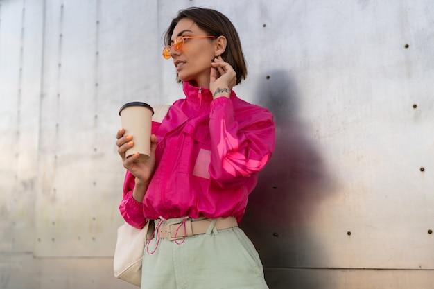 Elegante donna sportiva con acconciatura corta in posa con una tazza di caffè