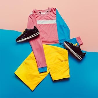 スタイリッシュなスポーツブラウスとパンツ。パステルトレンド。ファッションアクセサリー。最小限のスタイリッシュな服フィットネス服上面図