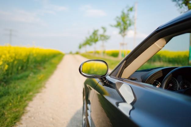 Стильный спортивный автомобиль на сельской дороге возле поля изнасилования