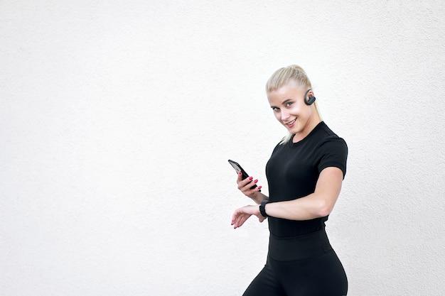 Стильная спортивная женщина в черной спортивной одежде, слушает музыку и проверяет программу тренировок на умных часах